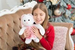 O brinquedo pequeno o mais bonito nunca Brinquedo pequeno do coelho do abraço da menina O melhor brinquedo do Natal Menina com o  fotos de stock