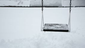O brinquedo vazio do balanço no parque no inverno e no dia nevado é balancê video estoque