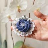 O broche feito a mão pequeno feito da sarja de Nimes encontra-se na palma da mão Fotos de Stock Royalty Free