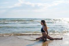 O bruenette da mulher com cabelos longos no biquini azul está esticando no litoral Vista lateral imagens de stock royalty free