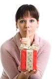 O brunette atrativo mostra o presente de Natal secreto Fotografia de Stock