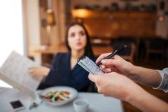 O buisnesswoman novo agradável senta-se na tabela no restaurante Aponta no menu e no olhar na empregada de mesa Escreve a ordem n imagens de stock royalty free