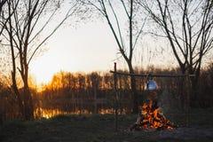 O bule com ch? pendura sobre o fogo no por do sol do riverbank fotos de stock