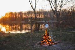 O bule no fogo prepara o ch? Por do sol alaranjado fotos de stock royalty free