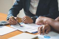 O businessteam novo trabalha em estatísticas e em gráficos de negócio, discutindo as cartas e os gráficos que mostram os resultad imagens de stock