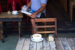 O cálculo de gastos da xícara de café em uma tabela pequena de madeira, um cappuccino, café com o leite, perfumado um cappuccino Foto de Stock