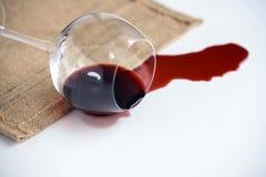 O cálice de vidro caído na tabela dele derrama para fora o vinho tinto, o conceito imagem de stock royalty free