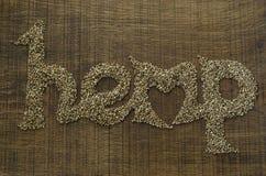 O cânhamo da palavra escrito artisticamente em sementes de cânhamo em um cho de madeira Fotos de Stock