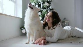 O cão branco do Natal levanta perto do proprietário no photoshoot na árvore próximo decorada acolhedor do Xmas da atmosfera filme