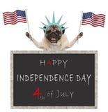 O cão de cachorrinho do Pug com bandeira americana e a estátua da liberdade coroam, atrás do quadro-negro com o texto feliz 4o ju Fotografia de Stock Royalty Free