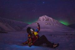 O céu ártico do aurora borealis da aurora boreal protagoniza no homem Svalbard da menina do blogger do curso de Noruega na cidade imagem de stock