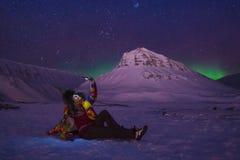 O céu ártico do aurora borealis da aurora boreal protagoniza no homem Svalbard da menina do blogger do curso de Noruega na cidade foto de stock