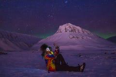 O céu ártico do aurora borealis da aurora boreal protagoniza no homem Svalbard da menina do blogger do curso de Noruega na cidade imagens de stock