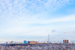O céu com as nuvens brancas sobre casas e a tevê elevam-se Imagens de Stock