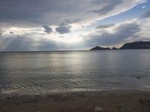 O céu dramático com sol irradia das nuvens na praia de Agios Georgios Pagon da costa de mar na ilha de Corfu, Grécia na hora dour fotos de stock