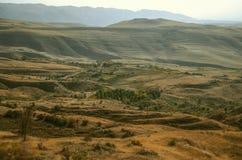 O céu em um embaçamento e em um vale montanhoso, com campos do outono nas montanhas do cume de Gegham fotos de stock