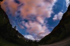O céu estrelado com as nuvens coloridas borradas do movimento e luar brilhante Caro paisagem nos cumes europeus, fisheye u da noi Fotos de Stock Royalty Free