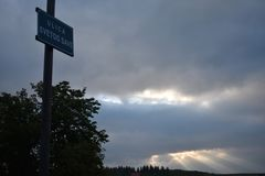 O céu nebuloso do amanhecer e o cargo da lâmpada com a chapa da rua unida nela imagens de stock royalty free