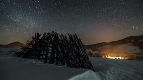O céu noturno com as estrelas que movem-se sobre o país rural do inverno com quadro de madeira, lapso de tempo da astronomia, zor video estoque