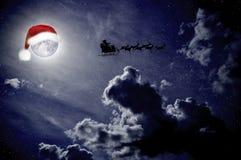 O céu noturno com chapéu de Santa é posto sobre a lua, o trenó de Santa imagens de stock