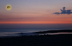 O céu noturno cor-de-rosa e azul mágico bonito com nuvens e Lua cheia e estrelas aproxima o mar fotografia de stock royalty free