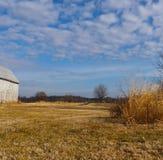 O céu, nuvens, celeiro, trigo, grama, árvores faz toda uma parte nesta cena pitoresca da terra do inverno imagem de stock royalty free