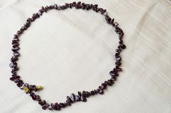 O círculo é feito dos grânulos bonitos fêmeas, colares de pedras escuras marrons, ambarinas com um fundo da tela bege foto de stock