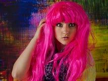 O círculo grande eyed a menina com uma peruca cor-de-rosa brilhante foto de stock