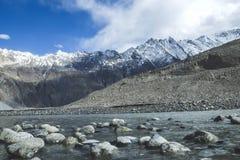 O córrego da água de fluxo entre a neve tampou montanhas na escala de Karakoram imagem de stock royalty free
