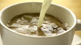 O córrego de derramamento ordenha em um copo do café no movimento lento video estoque