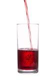O córrego do suco flui em um vidro Fotografia de Stock Royalty Free