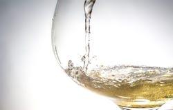 O córrego do vinho que derrama em um close up de vidro, vinho, respingo, bolhas, efervesce Fotos de Stock Royalty Free