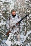 O caçador com a arma nos arbustos no inverno Fotografia de Stock