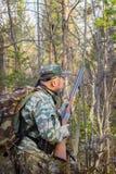 O caçador desengaça o pássaro na floresta Fotografia de Stock Royalty Free