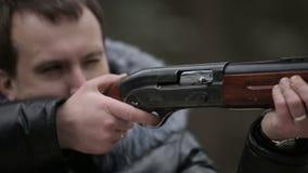 O caçador dispara em um movimento lento do cartucho da arma e da mosca vídeos de arquivo