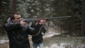 O caçador dispara em uma arma e o cartucho da mosca e o segundo homem proibem-no disparar video estoque