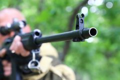 O caçador do homem está visando a arma Observando o tambor de arma em Imagens de Stock Royalty Free