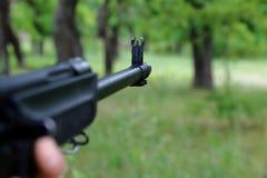 O caçador está visando a arma Observando o tambor de arma no Imagens de Stock Royalty Free