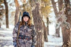 O caçador fêmea na camuflagem veste pronto para caçar, guardando a arma a fotografia de stock royalty free