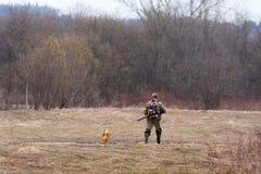 o caçador no campo com um cão Fotos de Stock Royalty Free