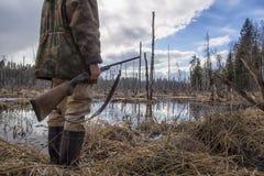 O caçador realiza em sua mão um rifle velho da caça Fotos de Stock
