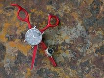 O cabeleireiro à moda vermelho scissors com punhos graciosos em um fundo oxidado, no meio da mentira do instrumento um wristwat p Foto de Stock