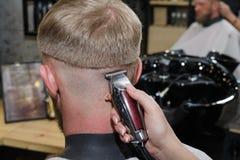 O cabeleireiro corta o cabelo do cliente no cabeleireiro imagens de stock