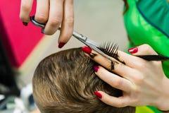 O cabeleireiro corta a criança Close-up do corte de cabelo foto de stock