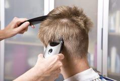 O cabeleireiro corta o cliente Imagens de Stock