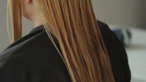 O cabeleireiro corta uma mulher com cabelo louro longo Close up do corte de cabelo vídeos de arquivo