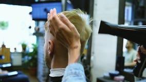 O cabeleireiro da menina seca o cabelo a um homem em um sal?o de beleza video estoque