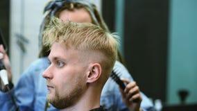 O cabeleireiro da menina seca o cabelo a um homem em um sal?o de beleza filme