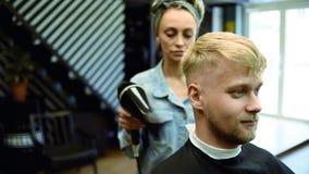 O cabeleireiro da menina seca o cabelo a um homem em um sal?o de beleza vídeos de arquivo