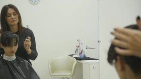 O cabeleireiro do ` s da mulher faz a denominação de seu cabelo no cabelo curto Movimento lento vídeos de arquivo